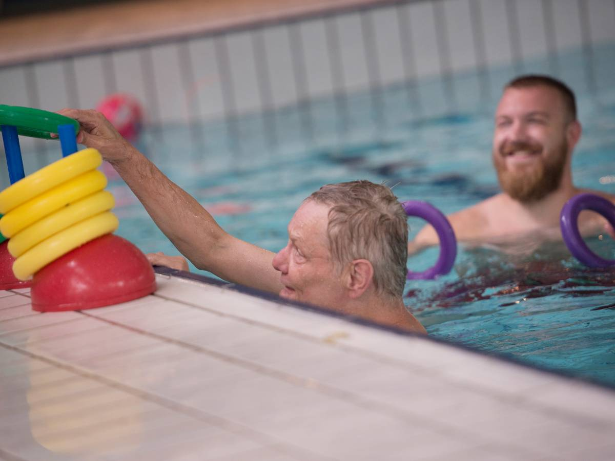 Begeleider en cliënt in zwembad activiteit met gele ringen