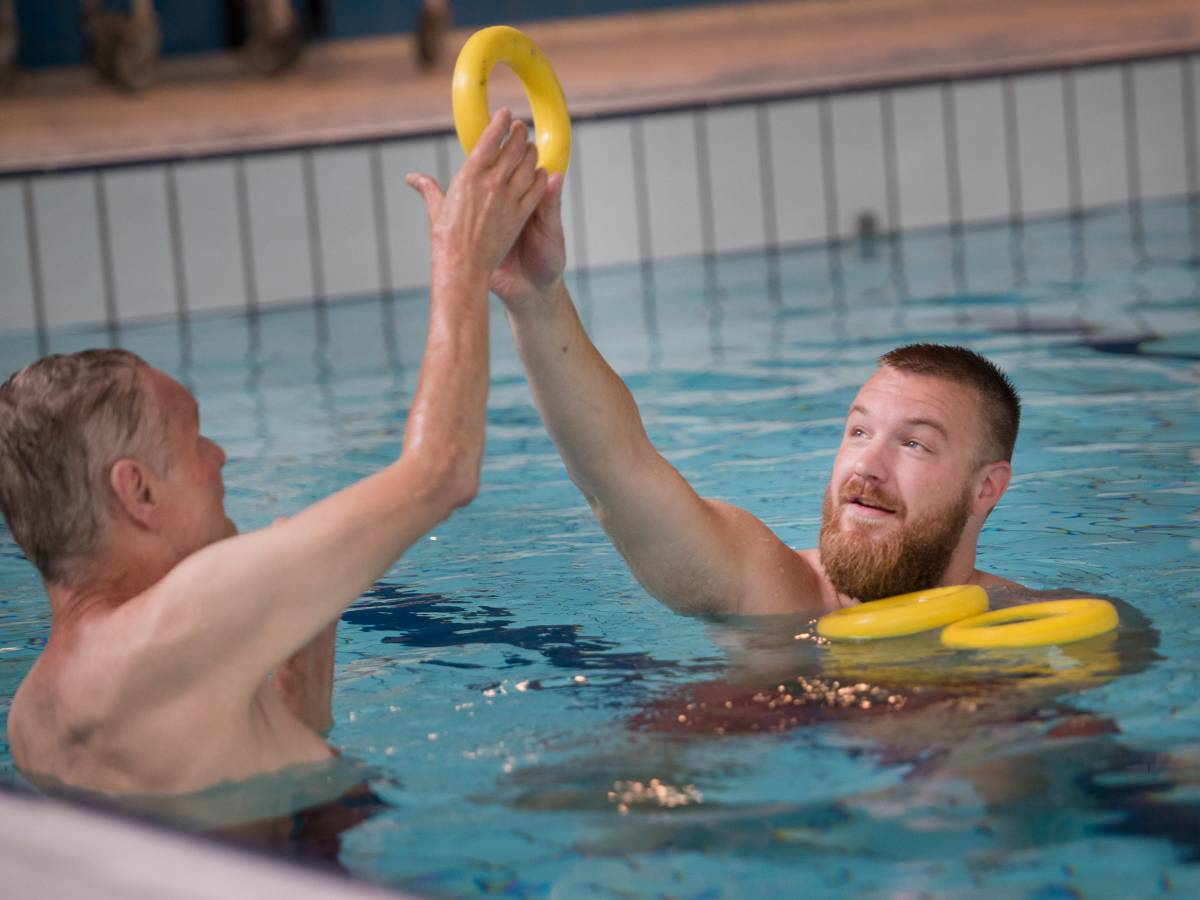 Begeleider en cliënt in zwembad activiteit met paarse ringen